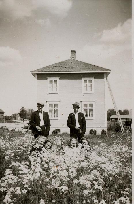 På bilden här ovan står Karl Lillkull t.v och Yngve Söderqvist och bland blommorna gömmer sig 4 unga damer, fr.v Elvi Långfors, Mildrid Forslin, Inga Klemets och Ewy Forslin. Bilden är tagen från väster, landsvägen syns till vänster på bild och i vänstra kanten syns lite av Dahlroos Arvids hus. I högra kanten syns uthusen hos Eskil Agnäs.
