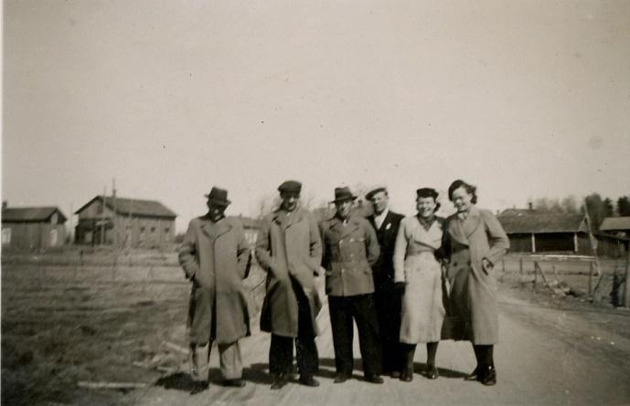 Här står Arvid Lillkull, Egil Holmudd, Einar Storkull, Egil Storkull, Elvi Holmudd och Lilli Eklund på landsvägen utanför Sigrids kafé. I bakgrunden till vänster syns de båda gårdarna på Antas.