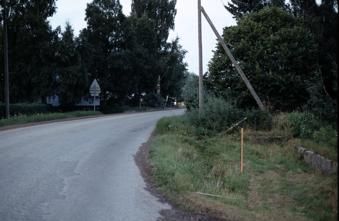 Då Rurik Norén rev ner gården så lämnade han stenfoten kvar, som syns i gräset till höger här på Ingmar Rosengårds foto. På andra sidan vägen skymtar Klåvus gård.