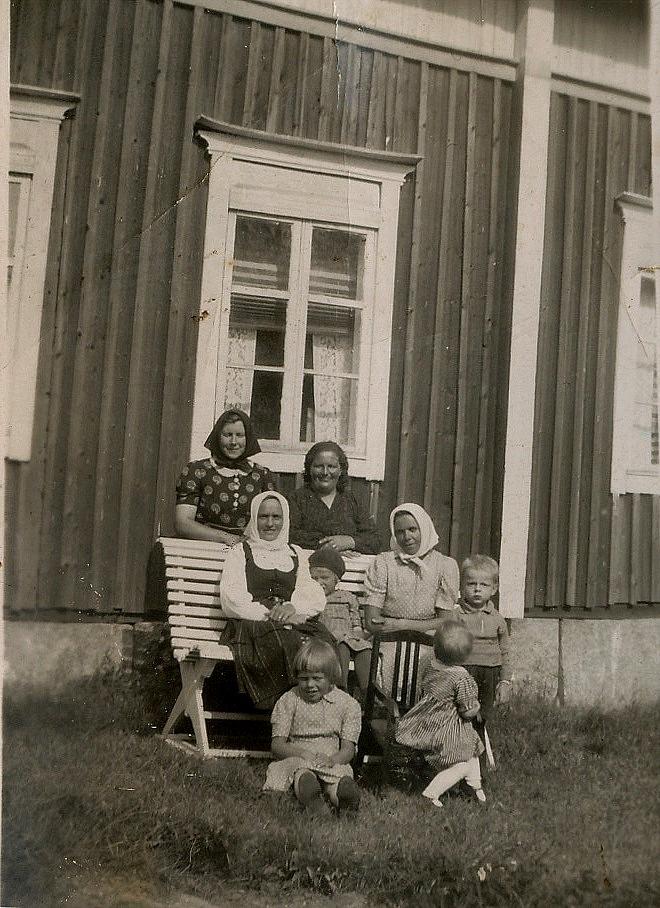 Bakom bänken står Signe Nyström och Hulda Norrgård, på bänken sitter Hulda Lindell och Jenny Lindell. Längst till höger står Alf Norrgård, sittande fram Göta Lindell.