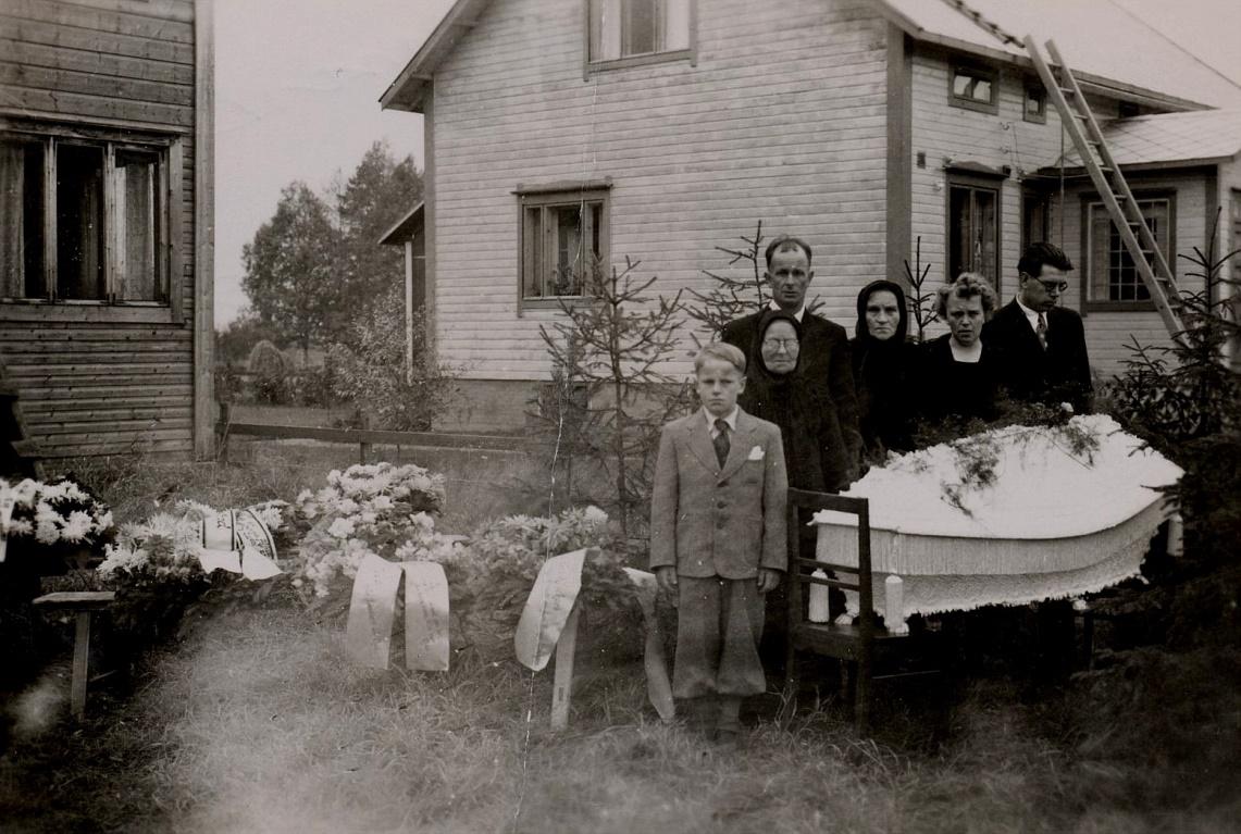 """Vera Norén som var född år 1915 gifte sig år 1942 med Lennart Klockars (1912-1984) från Lappfjärd. År 1943 fick de sonen Max och de bodde i Dagsmark och sedan flyttade de till Kristinestad. År 1950 flyttade de till Lappfjärd då deras gård blev färdig i Idbäcken. År 1952 dog Vera plötsligt och här på fotot står sonen Max, som då var 9 år gammal. Bakom honom står hans farmor Maria """"Mina"""" Vilhelmina (1879-1959) och bakom henne står pappa Lennart. Bredvid Lennart står Fina Norén och till höger står Veras syskon Aina och Rurik. Huset i bakgrunden tillhörde Holger och Edith Hammarberg. Foto: Ilta-Lilja Klockars."""