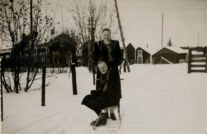 """Bakom flickorna Verna Agnäs och Gerda Klåvus syns """"Måg-Jåssas"""" eller Klåvus gård, fotograferad från öster."""