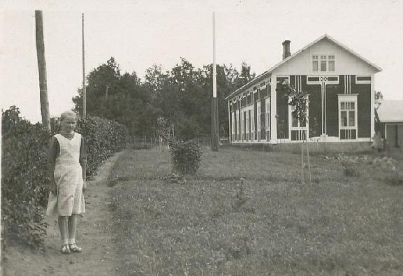 Agnäs gamla gård var en extra dekorativ men i övrigt tidstypisk bondgård. Här står yngsta dottern Verna Agnäs (f. 1925, gift Björkskog, bor i Lappfjärd).