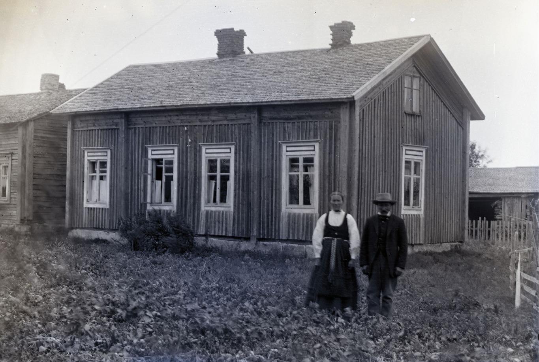Här står Klemets Emil och Manda framför gården medan den ännu stod uppe i centrum lite öster om folkskolan. Fotot taget av Viktor Nylund, kanske 1915.