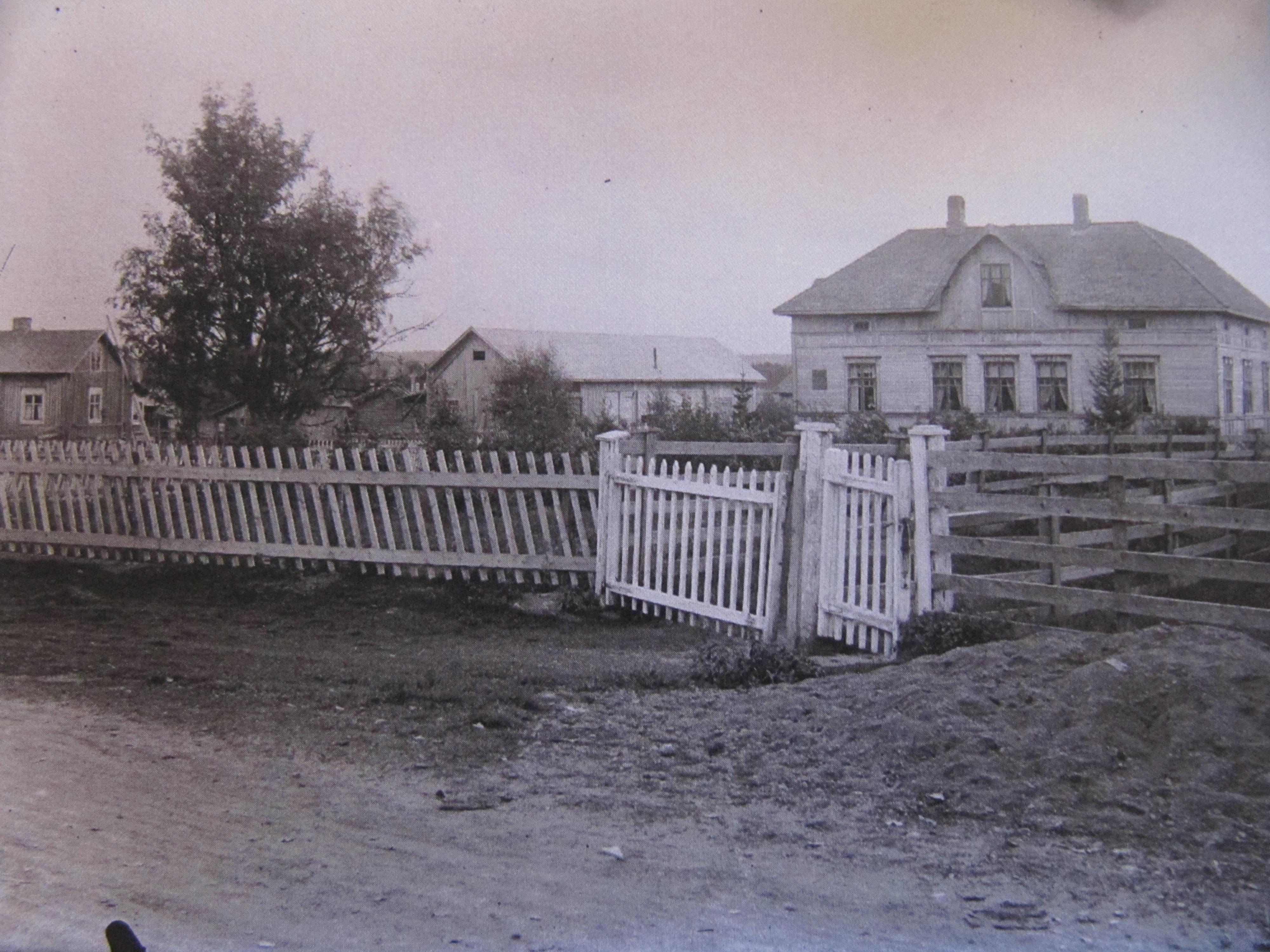 På den här bilden som är nyare så ser vi att gården är bortflyttad, den stod alltså bakom trädet till vänster. Kvar står den andra stugan i vänstra kanten som revs i något skede. Till höger den ståtliga Klemets huvudbyggnaden som byggdes i början på 1900-talet, alltså den som revs ner 2006-2007. Grinden är den så kallade Lillgrinden som ledde ner till folkskolan. Foto: Viktor Nylund.
