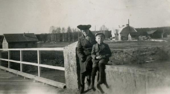 På den här bilden från 1946-47 sitter Beda Westerback tillsammans med systersonen Bo Skogman på broräcket. Till vänster på bilden syns Valters garagebyggnad och till höger Dagsmark Andelsmejeri.