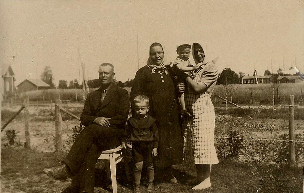 """Sittande Emil Norrgård och bredvid honom sonen Alf (1936-1955) stående Hulda Norrgård och t.h. Amanda """"Rebeck-Manda"""" Lillkull med en son i famnen."""