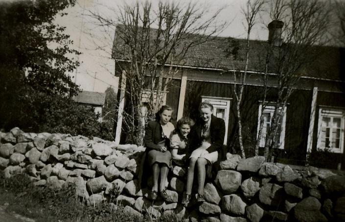 Bakom den vackra stenmuren byggde Agnäs Henrik och Mina sin sytningsstuga där de bodde till sin död. Den stod med gaveln eller kanske hörnet mot landsvägen. På muren sitter fr.v. Alice Gröndahl, Alice Björklund och Gerda Klåvus.