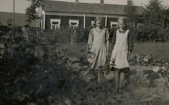 """I samband med storskiftet blev Agnäs Henriks hela hemman utflyttat till Åbackan, lite västerut från Hällbacks gård. Men de flyttade aldrig dit någon gård, utan de köpte i stället Rosenbacks hemman som fanns nära folkskolan av Viktor och Edla Maria Rosenback och fick på det viset tillgång till """"Måg-Jåssas"""" gård, som syns på fotot bakom flickorna. Flickorna är Gerda Klåvus tillsammans med kusinen Verna Agnäs."""