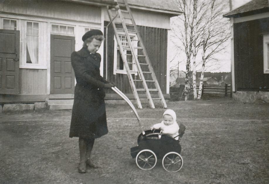 Ellen Skogman med sonen Bo på Westerbacks innergård, till höger syns hörnet av lillstugan där Ellens faster Amanda bodde. I bakgrunden skymtar mejeriet.