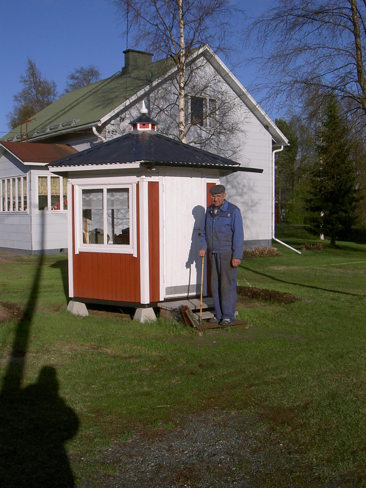 Här står Arvid Dahlroos framför det egenhändigt byggda lusthuset där hemma på gården, året är 2003. I bakgrunden Else Korsbäcks gård.
