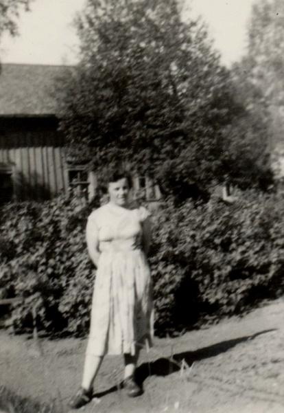 På fotot Anita Björklund framför den gamla bondgården.