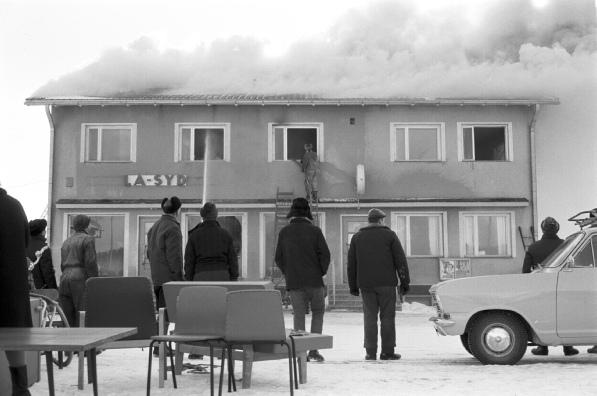 Byssborna kan bara stå och se på då brandmännen gör vad dom kan för att rädda byggnaden. En del av bankens lösöre kunde räddas medan största delen av La-Syds inventarier förstördes i den svårsläckta branden. Foto: Rafael Olin, Österbottens Traditionsarkiv.