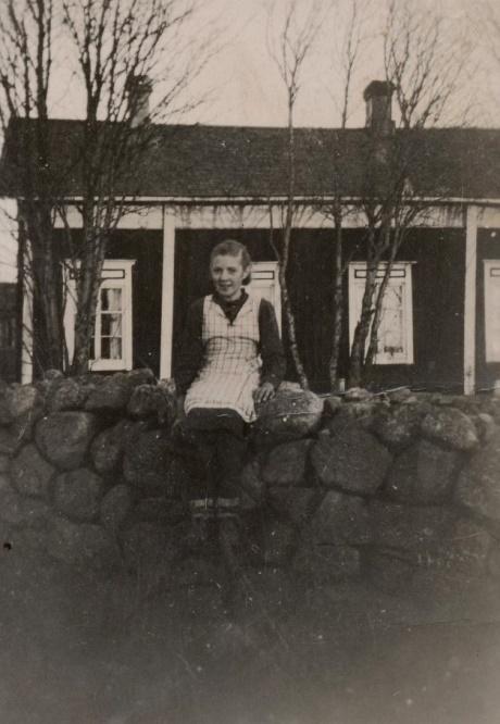 Mittemot Antas gård fanns en hög stenmur nära landsvägen, där Alice Björklund klättrat upp. I bakgrunden står Agnäs-Hindriks och Minas sytningsstuga.