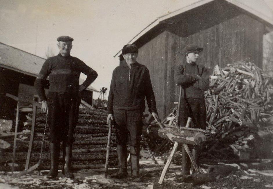 Här på vedbacken står Frans Agnäs med bågsågen, i mitten står hans far Henrik Agnäs och pojken till höger som ser mot folkskolan är Eskil Agnäs.