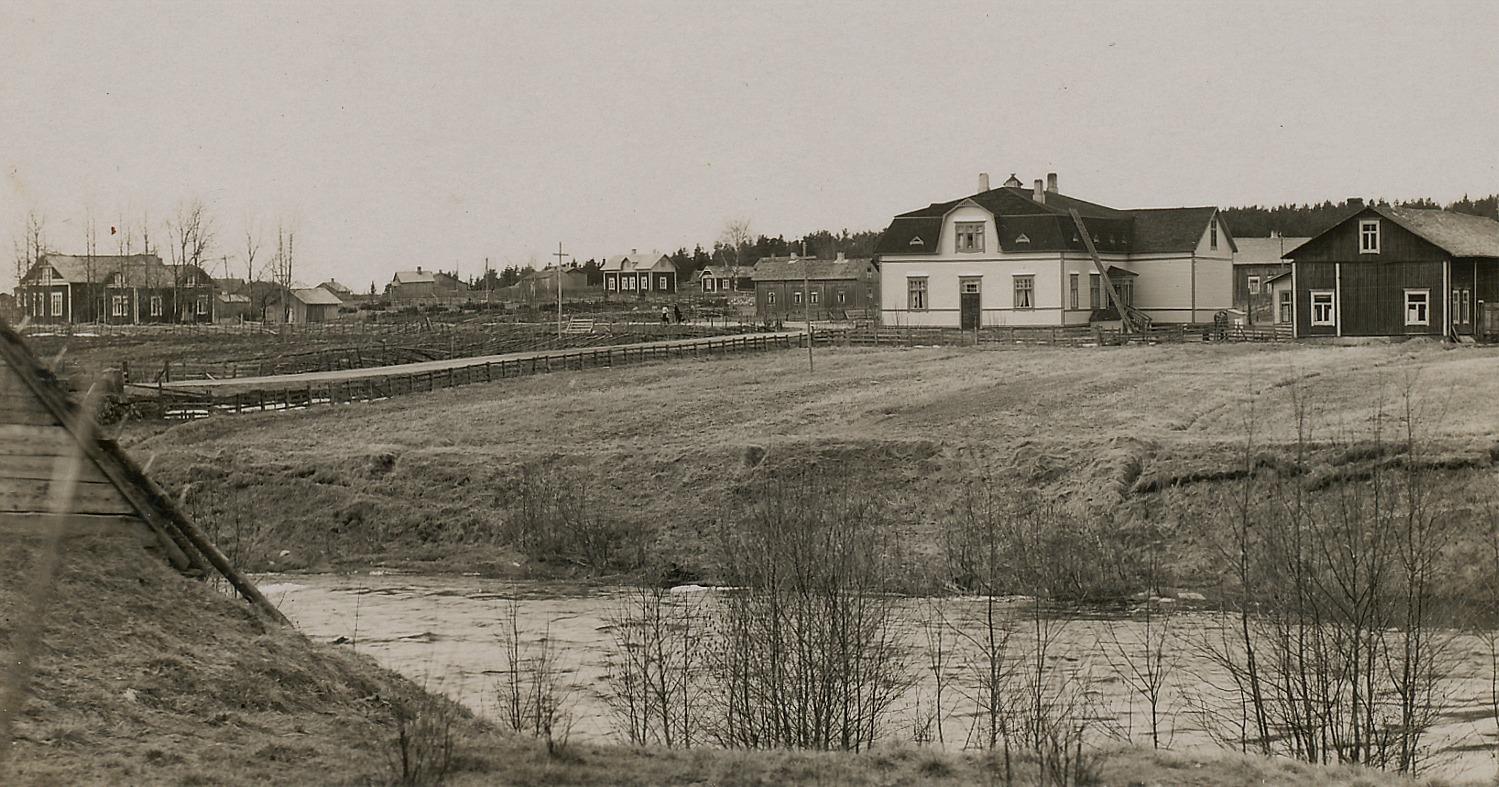 Längst till vänster syns ungdomsföreningens hus Majbo, uppe på backen syns Lill-Skräddarinas hus, som numera ägs av Rintamäki. Lill-Skräddarinas gård stod tidigare mellan folkskolan och Klemets bondgård. Följande gård är Åsinas-Viktoras som nu är i Rosengårds ägo och längst till höger står J. H. Storkulls ståtliga affärshus. I uthusbyggnaden som syns i högra kanten fanns magasin och bostadsutrymmen.