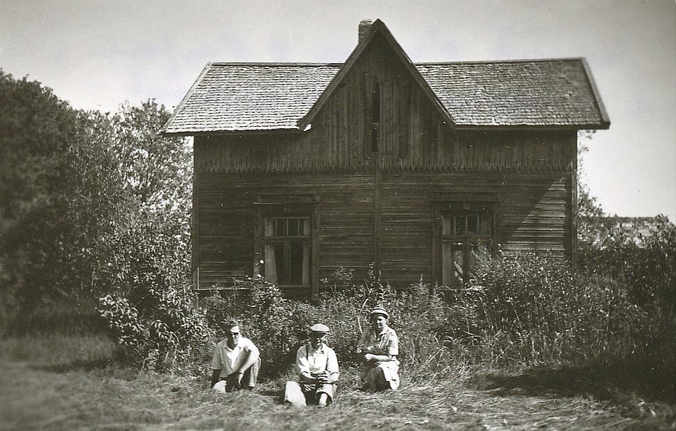 Framför Dragås-Hildas stuga sitter hennes son Frans i mitten och bakom honom hans hustru Lydia och deras måg Kalevi Häyry från Vasa.