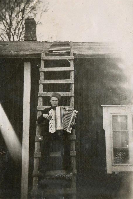 Här sitter Veli Kangas på stegen och spelar på sitt dragspel.