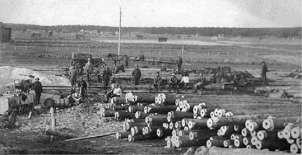 På bilden Axel Lillträsk med sina mannar som borrar stockar för vattenledningen. Borren drevs av en oljemotor som syns t.v. Det här vattenledningsprojektet fick ett tillfälligt avbrott då Axel mördades en kväll i december 1932 men det återupptogs av släktingarna och flera lappfjärdsbor anslöt sig och ledningarna användes under många år.