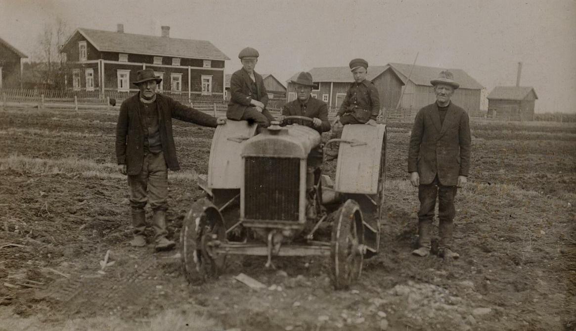 """På bilden från 1926 står """"Kaalas-Hindrik"""" till vänster och J.H. Storkull till höger. Gunnar sitter på traktorn med Einar och Eskil på sidorna. I bakgrunden Krook-Josefs gård före den blev tillbyggd med en vindsvåning. År 1929 skulle ju mejeribyggnaden resa sig på åkern bakom traktorn."""
