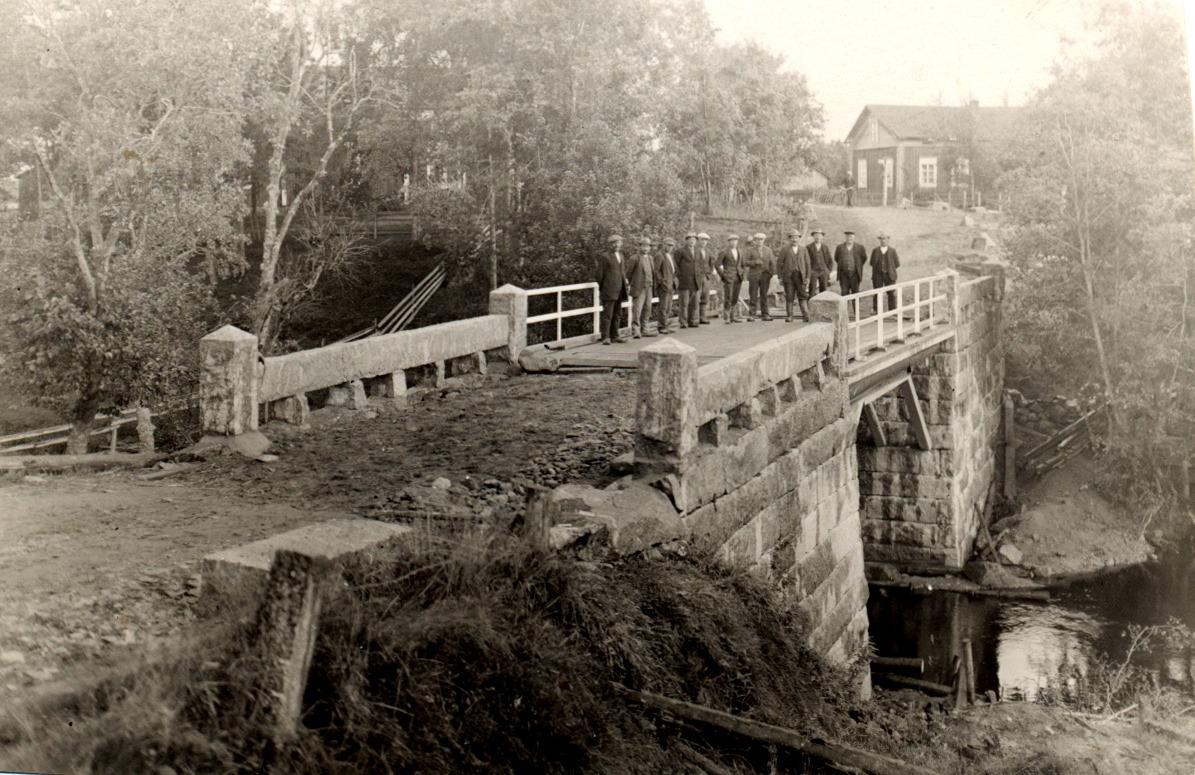 På den här bilden ser vi att lillstugan flyttats över vägen, där den fortfarande står. Detta foto är från början på 1930-talet då en grupp stenhuggare från Vanhakylä byggde den nya Lillbron.