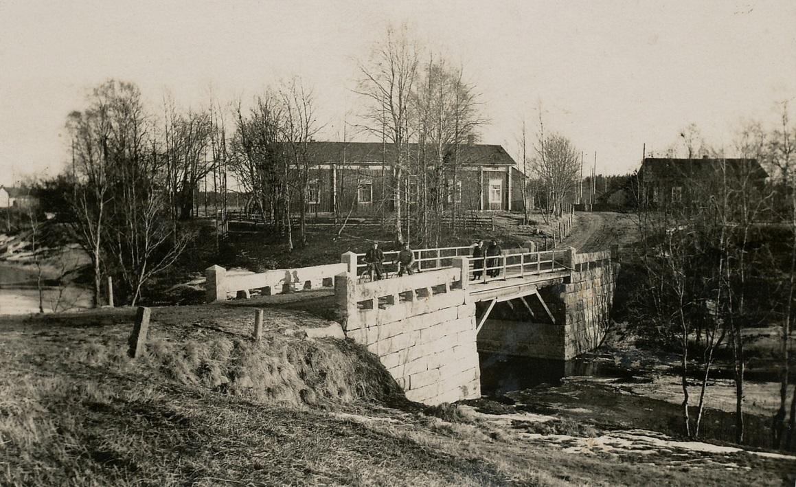 På denna bild från 1930-talet ser vi den nya stenbron över Lillån och bakgrunden syns den stora bondgården bra. Här ser vi också att sytningsstugan flyttats över vägen till den plats där den fortfarande står.