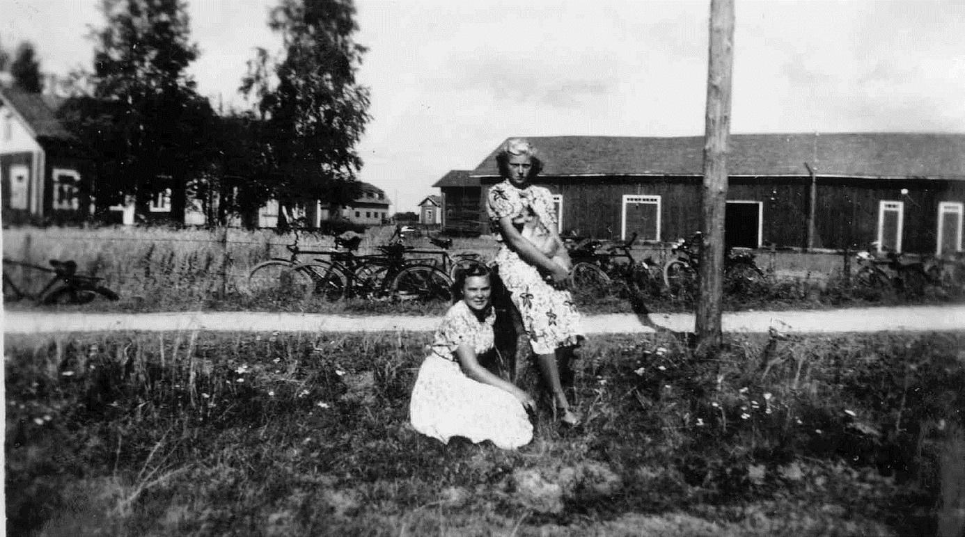 """På bilden från 1950-talet ser vi Eklunds gamla gård i bakgrunden t.v. , mitt i bild skymtar Westaras smedjan och Koll-Minas gård. Det är Greta Gröndahl, gift Lindell som sitter och Ruth Mitts som står med hunden Nelly i famnen. Notera de många """"karavangnen"""" på andra sidan Lillsjövägen."""