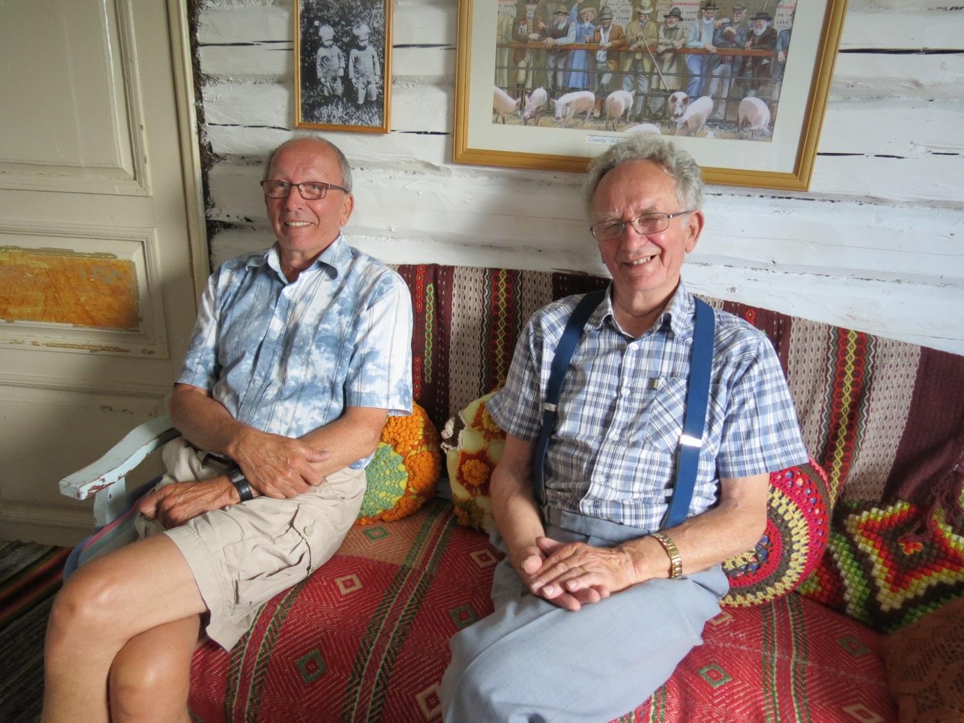 På detta foto från 2014 sitter tvillingarna Lars och Åke i soffan i sitt barndomshem. Ovanför Lars huvud en tavla med tvillingarna i unga