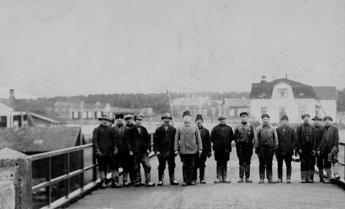 Denna grupp är fotograferad från den södra sidan, längst till vänster Josef Berglund och så finns där Hemming Nyholm, Emil Nyholm, Viktor Eklund, Karl Hemberg och många andra okända. Längst till vänster Vidbergs hus, Algot Rosengårds hus, i mitten Gunnar Långqvists långa bondgård och till höger handlanden Storkulls butik. Bilden från mitten av 1920-talet, möjligtvis 1928 då brolocket förnyades helt.