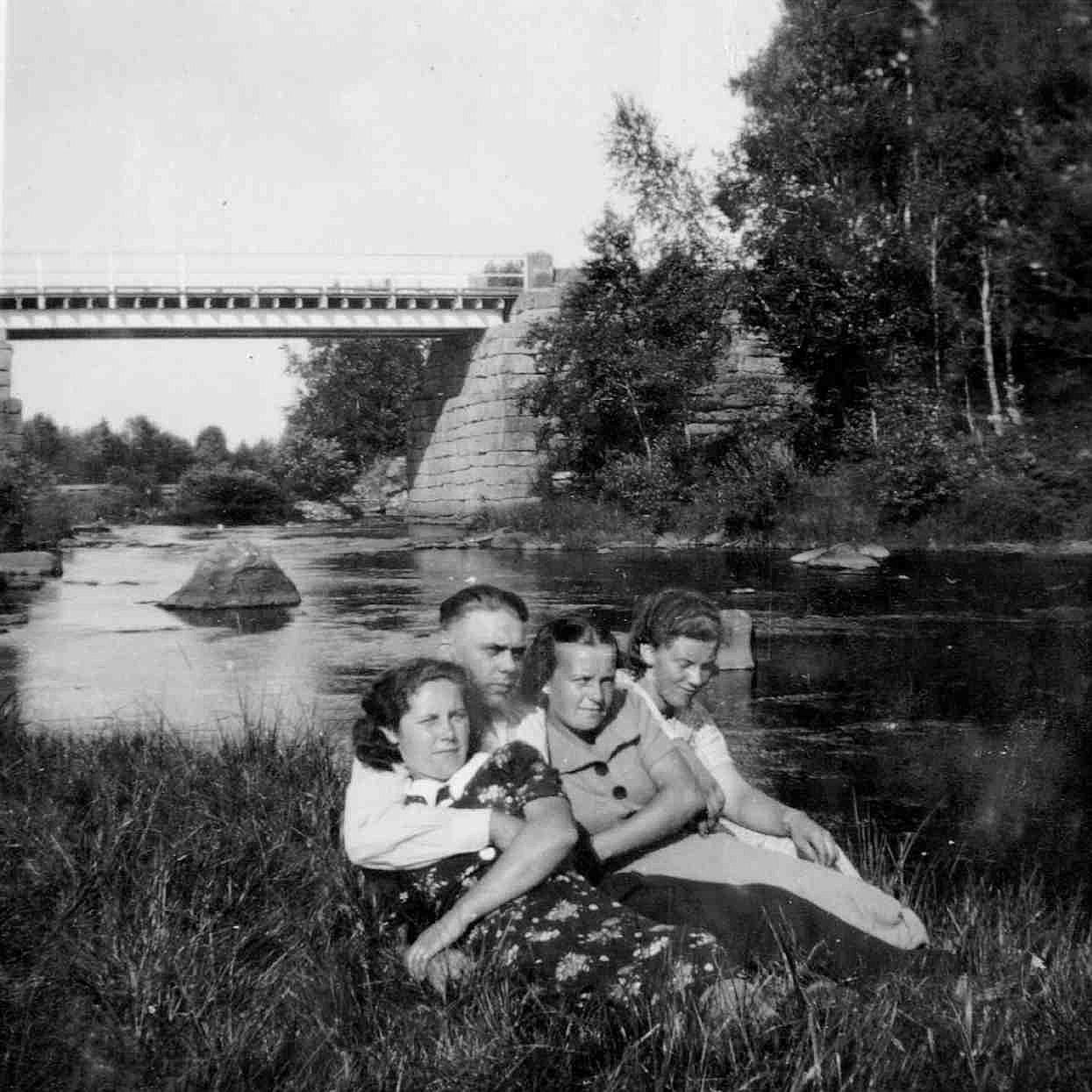 Här en grupp ungdomar nere vid ån med Storbron i bakgrunden.