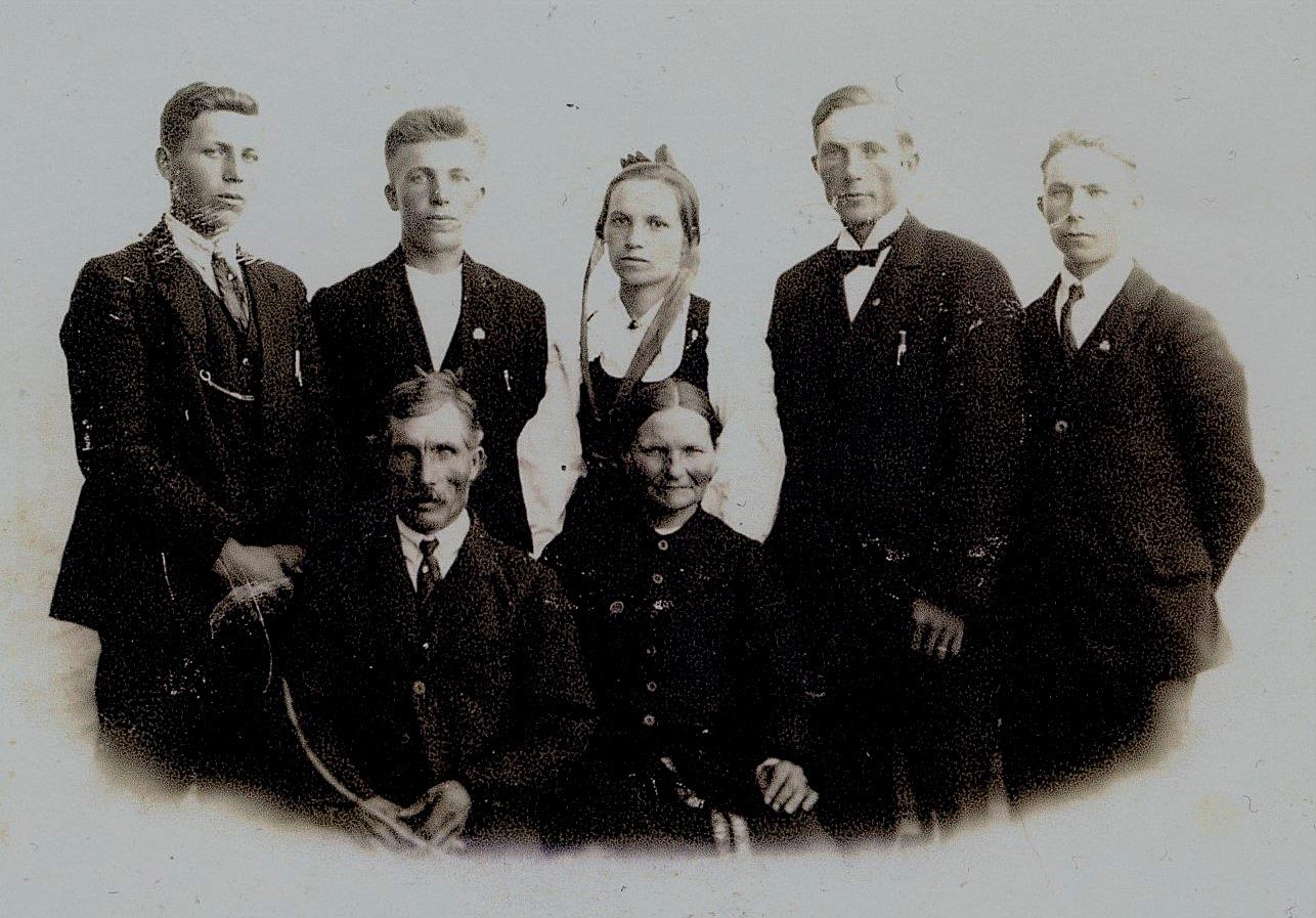 Här sitter Viktor och Maria Nyholm med barnen stående bakom, från vänster Evert, Leander, Hulda, Emil och Hemming.
