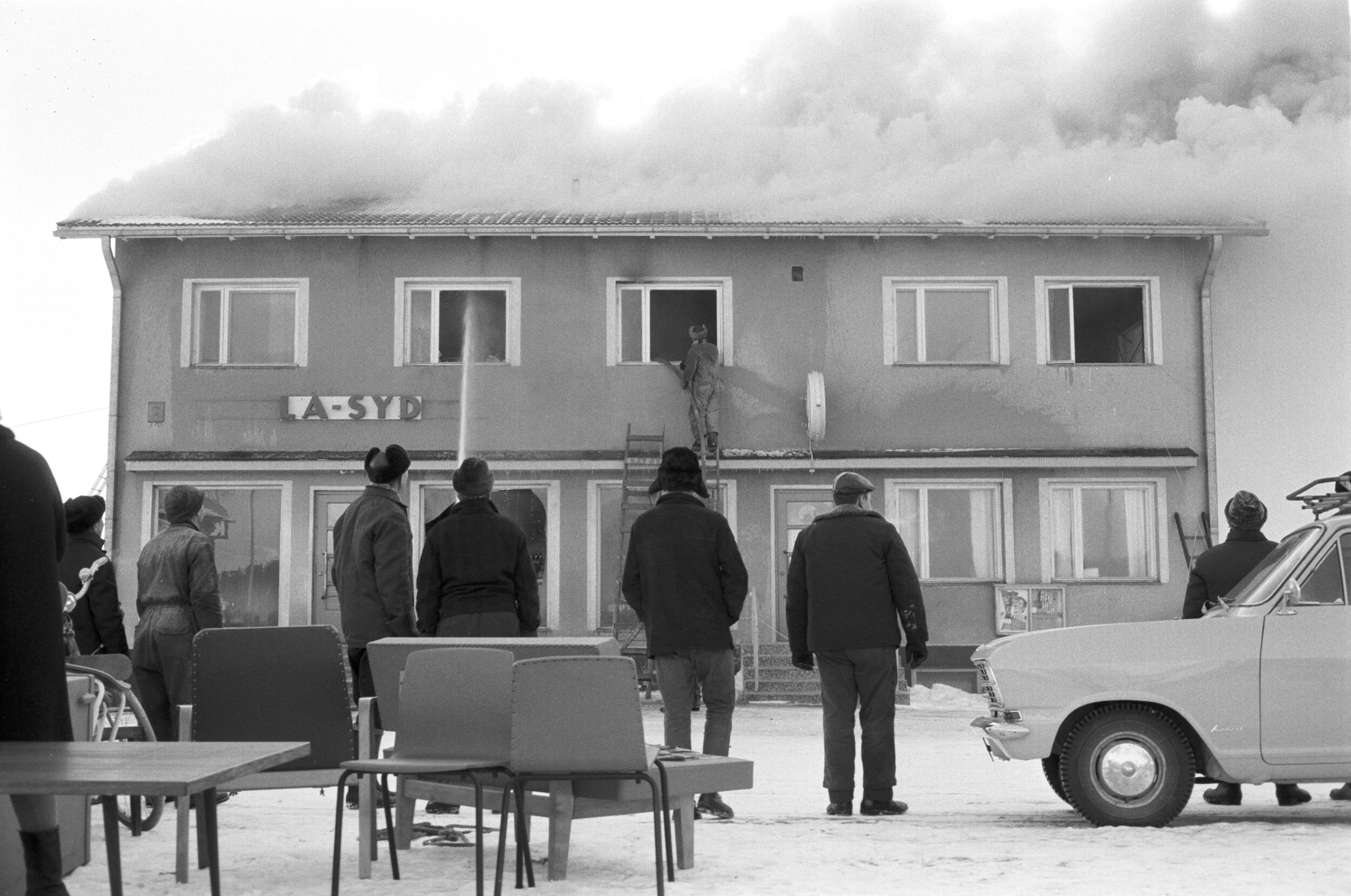 En del av inredningen från Sparbankens kontor kunde räddas medan själva byggnaden förstördes helt. Här står en del bybor och ser på då brandmännen försöker släcka elden.