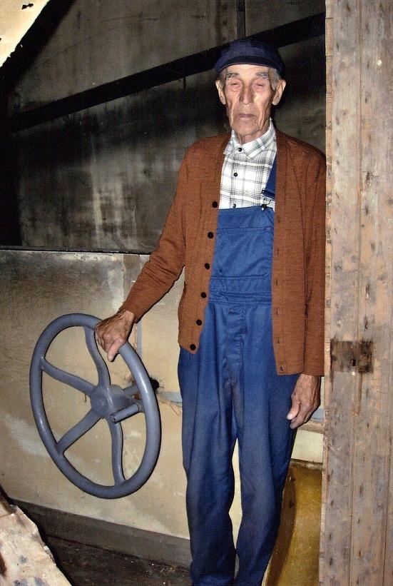Med den här ratten som Stig Björs håller i kunde man starta och styra turbinen så att luckor öppnas via axeln till vänster på den övre bilden.