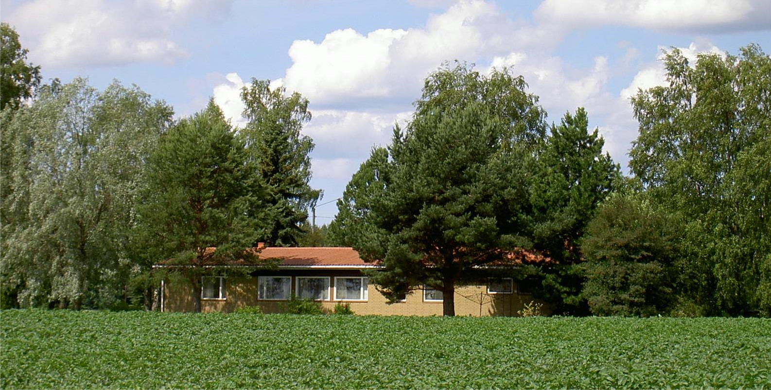 Den nya gården som byggdes 1969 ligger som sig bör inbäddad i grönska, omgärdad av potatisodlingar. Foto från sydost år 2004.