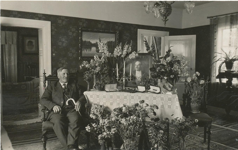 Här sitter Viktor bland blommor och presenter i sitt hem på sin 60-årsdag, år 1933.