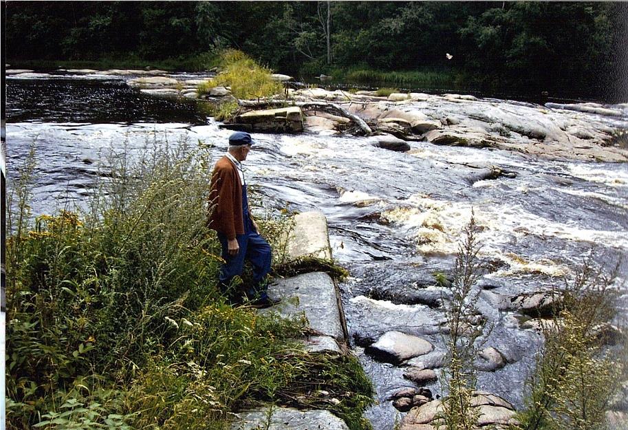 Stig Björs begrundar resterna av dammen vid Storfors på norra sidan av Lappfjärd å. År 1920 ansökte Storfors Ab om tillstånd att bygga en damm och år 1922 fick de tillstånd av generalguvernören i Vasa att ersätta den gamla dammen med en ny. Foto: Yliluoma.