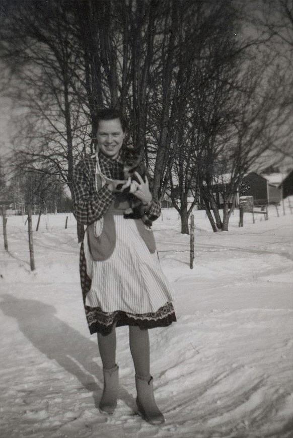 Här Ulla-Ellen Ånäs med sin katt. I bakgrunden syn Karl Lillkulls lillstuga.