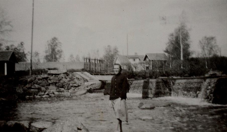 Här står Ellen Ånäs nedanför dammen vid Pärus-Fors. Kvis Olofs gård syns i bakgrunden.