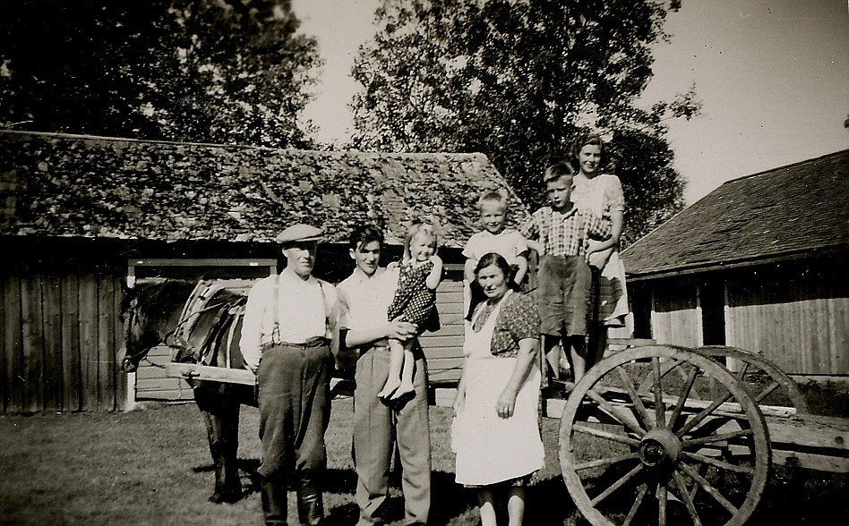 Här står Egil Mannfolk med dottern Mayvor i famnen. Till vänster står hans far Erland Mannfolk (1895-1972) och mitt i bild hans mor Elsa (f. i Sideby 1897-1982). Pojken bakom Elsa torde vara Tage Mannfolk.