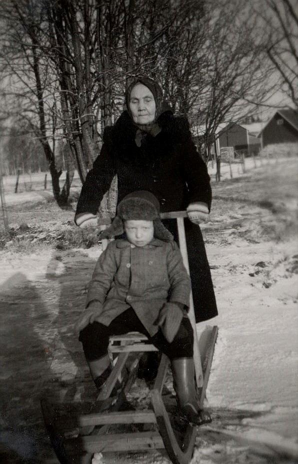 """Här """"Utteras""""-Selma Lillkull ut med träsparkaren. På sparkaren sitter """"Axelas"""" Håkan Söderqvist och i bakgrunden syns lillstugan där Lillkulls."""