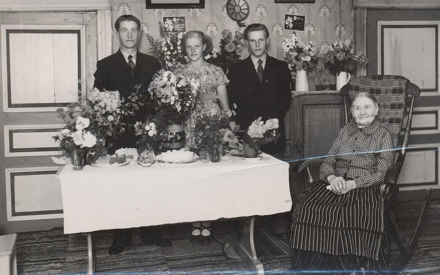I gungstolen sitter Karolina på sin 100-årsdag år 1951. Mannen till vänster är Uno Äbb och i mitten står Ruth och Alf Mitts.