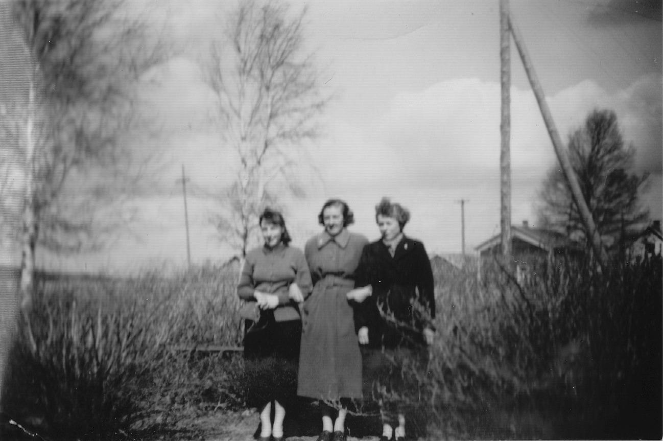 Bakom bärbuskarna på Brobackan skymtar Minas och Anakajsas gården. Flickorna på bilden är Birgit Lund, Alice Björklund och Marita Lindell.