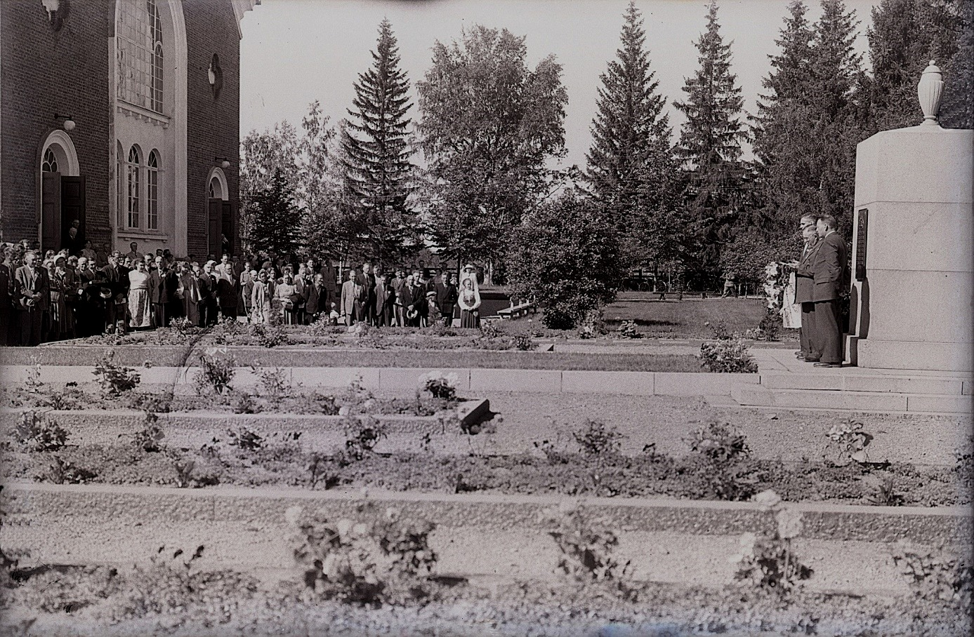 Här på Selim Björses foto är det en högtidlig uppvaktning vid krigargravarna framför kyrkan i Lappfjärd. Minnesmonumenten till höger i bild restes efter inbördeskriget, ungefär 1920. Det är tillverkat i Hangö och transporterades därifrån med tåg till Kristinestad och sedan med häst till Lappfjärd. Traditionsarkivet i Vasa.