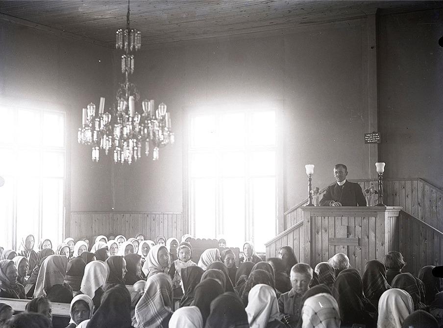 Sågägaren Viktor Nylund var en duktig fotograf och här har han lyckats över förväntan. Han fick med både takkronan, predikanten och en stor del av åhörarna. Ljuset kommer symboliskt vackert in från båda fönstren.