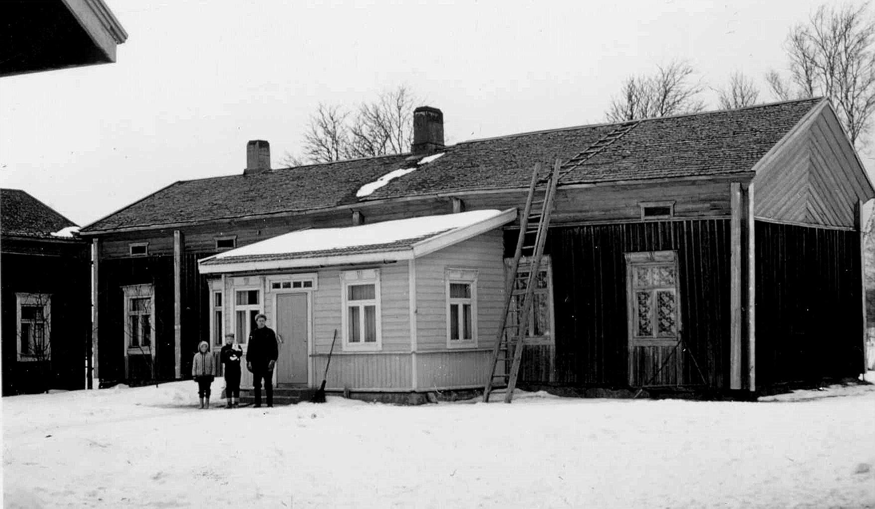 På bilden från 1950-talet står dåvarande ägaren Karl Lillkull med barnen Bernice och Gösta på gården. Kolla hur nära varandra lillstugan och huvudbyggnaden stod. Små barn rymdes emellan medan de vuxna fick gå runt gården för att komma till baksidan. Fotot taget från öster.