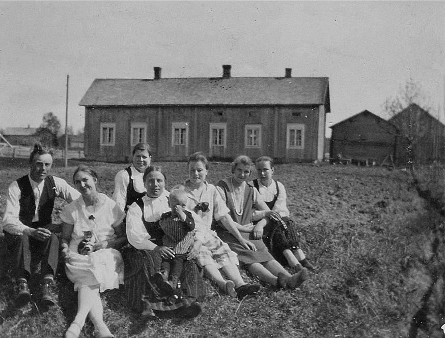 Fr.v. Anselm Lillkull (1902-1962) och hans dåtida fästmö Daga Kjellberg, hemma från Nykarleby som var lärare i Dagsmark åren 1925-1929. Den äldre damen mitt i bild är Adelina Lillkull (1876-1947) och snett bakom henne sitter sonhustrun Amanda (1904-1989) som var gift med Adelinas son Selim. I Adelinas famn sitter Nils Lillkull (1925-2002). Till höger om Nils sitter Aina (1904-1989) som gifte sig med Sigurd Löfgren. Längst till höger sitter Signe Ekberg (1909-1990) som gifte sig med Leander Nyholm. Men vem sitter bredvid Signe, andra från höger? Huset fotograferat från nordost år 1928.