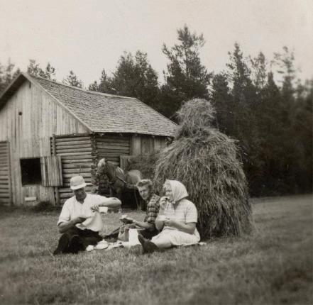 På detta fina foto som Lilli har tagit sitter Gunnar och Guldi i gräset tillsammans med sonen Harry. Säg vad man vill om höbärgning för hand men nog ser pausen för härlig ut! Bilden är tagen nära Bergåsen med Bymossen i bakgrunden. Se också hur den gamla stockladan har förstorats genom att skarva i den på mitten med bräder