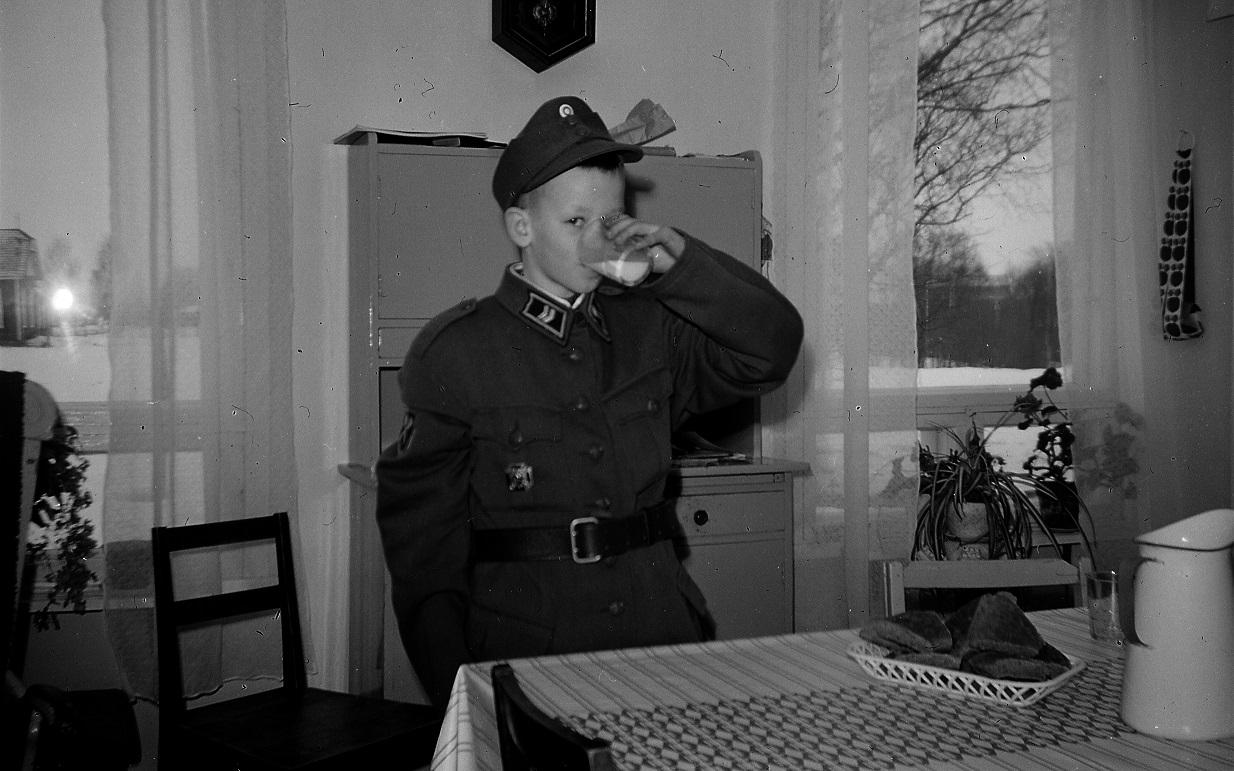 Lasse, 10 år provar storebror Per-Eriks militärkläder år 1966. I det ena köksfönstret syns bönhuset på granntomten.