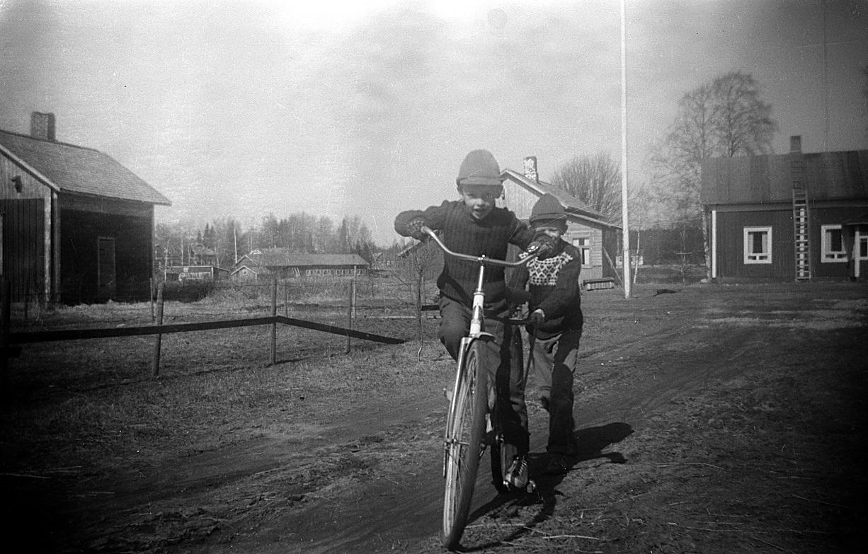 Lasse på cykeln och John springer efter och håller i. På andra sidan ån syns uthuset hos Åke Klemets. Folkskolan skymtar också i vegetationen.