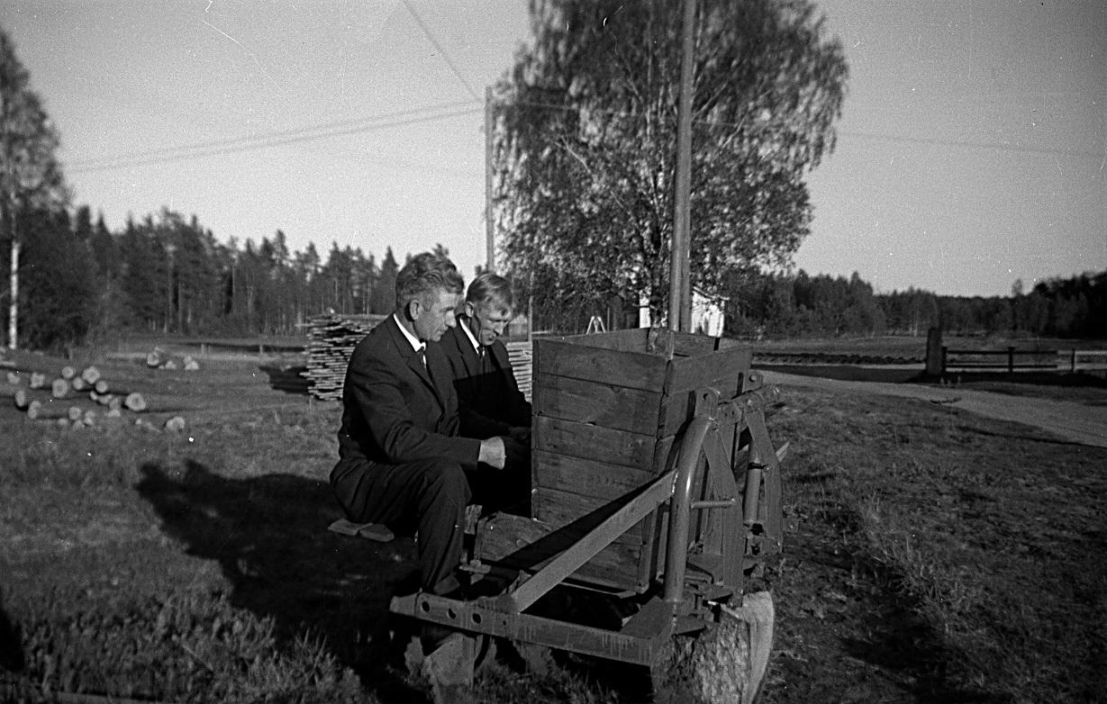År 1964 skaffades en riktig potatissättare och här prositts den av Ragnar och svågern Per Rosenstedt från Perus. Stockarna t.v skulle Ragnar hyvla till pärtor. Huset bakom björken är Arvid Lillkulls.